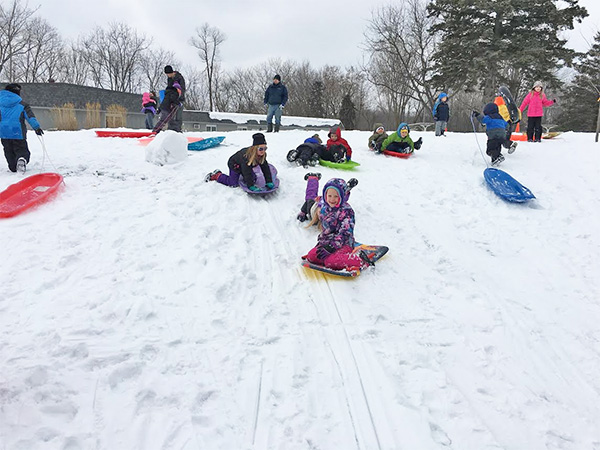 Kindergarten and first grade students enjoy sledding as a reward for meeting their reading goals.