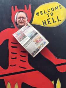 Belinda poses as the devil in Hell with the POST newspaper.