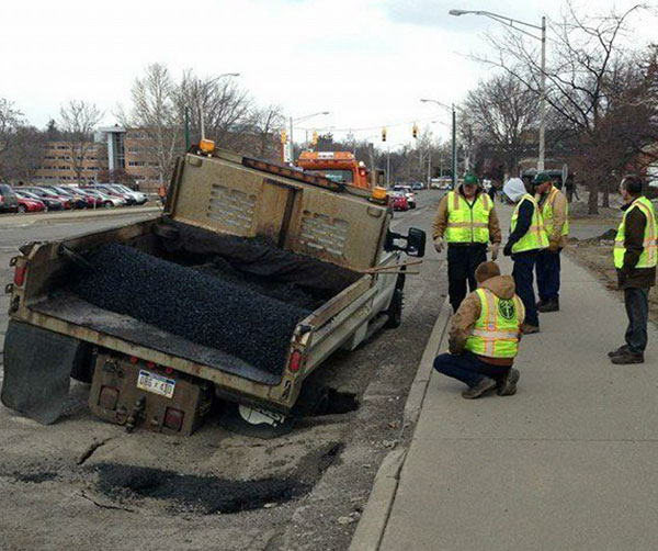 DPW workers try to figure out how to get their pothole repair truck out of a pothole.