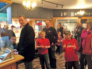 Mike Metzger, who started the first library card roundup in 1997, was on hand to help celebrate this year's event at the Kent Theatre. Here he poses with two Cedar Trails students. Movie-goers wait in line for popcorn at the library card  celebration at the Kent Theatre.