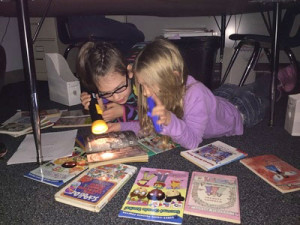 Second grade students Issabell Barr and Leda Gitchel reading with flashlights during Camp Out Day.