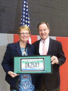 "Attorney General Schuette honored Assistant Superintendent of Teaching and Learning, Jo Spry, with a special license plate in a frame that reads ""OK2SAY."""