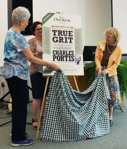 "Longtime One Book One County Montcalm supporter Carole Cole, on left, Montcalm Community College Library Director Katie Arwood, in back, and Carson City Public Library and Crystal Community Library Director Beth O'Grady unveiled the 2016 One Book One County selection, ""True Grit,"" by Charles Portis, during a May 19 kickoff celebration at MCC's Beatrice E. Doser Building on the college's Sidney campus."