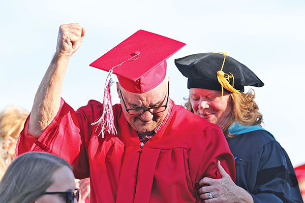 Erwin Duane Empie, 90, celebrates as he receives his diploma at the Cedar Springs High School graduation. Cedar Springs Superintendent Dr. Laura VanDuyn is behind him. Photo by K. Alvesteffer.
