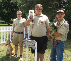 Austin Anderson (center) and friends Jacob Swinehart (left) and Andrew Watts (right) recently completed projects at Bellowood Dog Rescue to help Austin earn his Eagle Scout rank. The fence behind them and Welcome sign were two of the projects. Photo by J. Reed.
