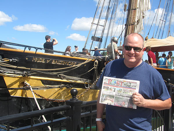 Steve Reed holding up The POST in front of the Pride of Baltimore II. Photo by Judy Reed.