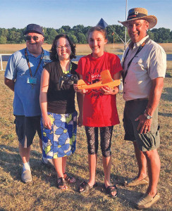 Kerissa Basso, 14, was the winner of the remote controlled airplane system given away by the Skyhawks. Pictured (from L to R): Skyhawks Club Treasurer Rick Steinport, CS Library Youth Services Miss Heidi, winner - Kerissa Basso, and Skyhawks Club President Eric Pipenger. Photo from the Wolverine Skyhawks facebook page.