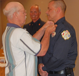 The above photo shows the promotion of Chris Paige to Deputy Chief as the 4 bugle collar brass is pinned on his uniform by his father, Mike Paige.