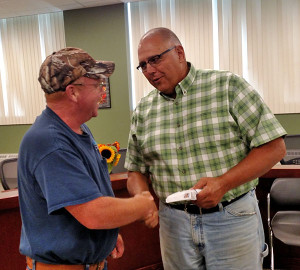 Dan Brown, left, presents CBDT president Kurt Mabie with a check to go towards a Veteran's Memorial Clock Tower. Courtesy photo.