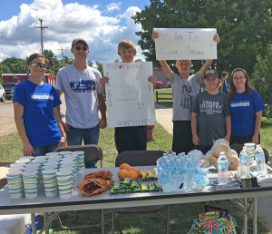 CTA staff and student athletes welcome runners to refreshment stand