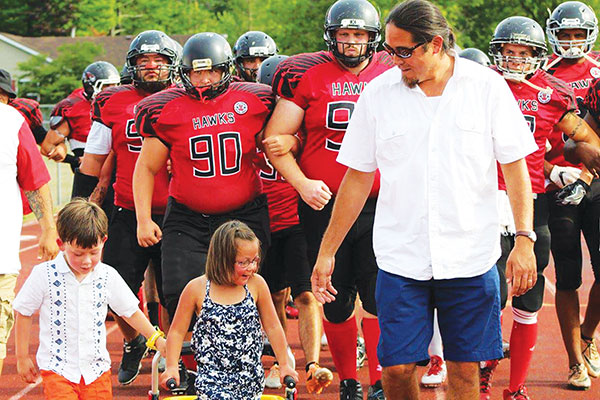 Three-year-old Libby Walla led the team onto the field to start the last home game they played on July 23. They raised $933 to help in her fight against periventricular leukomalasia.