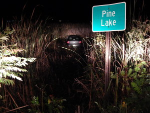 This car missed the stop sign at 17 Mile and Pine Lake Avenue Wednesday evening and drove into Pine Lake. Post photo by L. Allen.