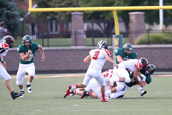 Red Hawks take down the Zeeland West ball carrier. Photo by K. Alvesteffer/R. LaLone.