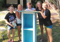 Lily and Chloe (far right) built the library this summer with fellow students, including (from left) Madeline VanSinger, Madison Layne and Alexandria Vanderhyde