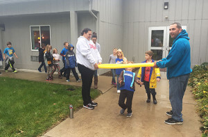 PA Volunteers hold a pool noodle for students to limbo under during the annual Walk-A-Thon.