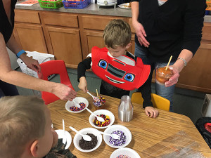 Liam Barr decorates his caramel apple in Miss Bostic's Kindergarten class
