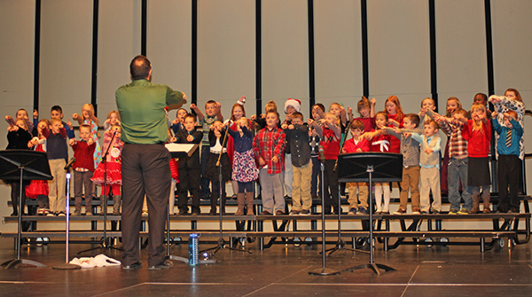 First and second grade students, conducted by Jeremy Holtrop, do riser-ography for their holiday music performance.