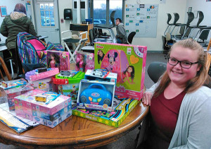 11th grade student Cortney Aspinall displays a few of the toys that were collected for Toys for Tots.