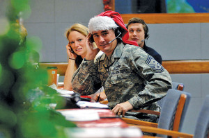Volunteer tracker Chief Master Sgt. Roderick Schwald, North Amercian Aerospace Defense Command and U.S. Northern Command first sergeant, answers calls from children and parents across the globe while at the NORAD Tracks Santa Operations Center on Peterson Air Force Base, Colo., Dec. 24. More than 1,200 volunteers from across the base and community join to cover shifts spanning the 23 hours of tracking that the North American Aerospace Defense Command hosts annually, dating back to pre-NORAD 1955. Photo by Air Force Master Sgt. Chuck Marsh/Released.