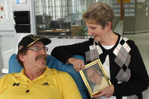 Lorraine Kieda, right, and her husband Al (in photo frame) began a life-saving tradition that their son Dan, left, carries on. Photo courtesy American Blood.