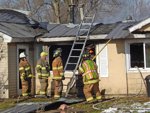Firefighters work to put out the fire and any hot spots. Post photo by L. Allen.
