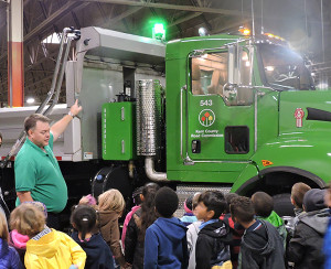 During a recent student tour on snow plow safety, Tim Fennema of the Kent County Road Commission explains to students about the new green lights they installed on trucks to increase their visibility and enhance safety for both motorists and crews. Photo courtesy of Kent County Road Commission.