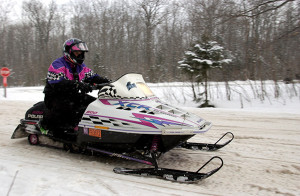 A rider heads out on a trail, having just made a highway crossing. Michigan has more than 6,000 miles of snowmobile trails to enjoy.