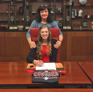 Hannah signing her letter of intent with Cedar Springs Cheer Coach, Anne Olszewski