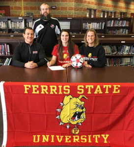 Maddie signing her national letter of intent with her parents and Soccer Coach, Justin Harnden