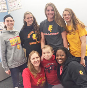 Players from the Ferris State University Girls Basketball team take time to pose with third grade student, Aiden Dood, after reading with his class.