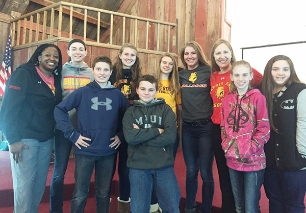 Players from the Ferris State University Girls Basketball team pose with several middle school students.