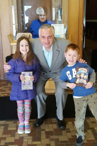 Mike Metzger, who founded the First Grade Library Card drive 20-plus years ago, is shown here with two of the attendees of the March is Reading month celebration at the Kent last week. Courtesy photo.