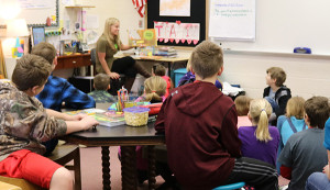 Board of Education member, Bayink, reads to students at Red Hawk during March is Reading Month.