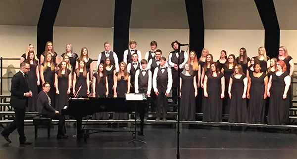 Charger Voices students perform at District Festival with teacher Jeremy Holtrop and pianist Bethany Holtrop.