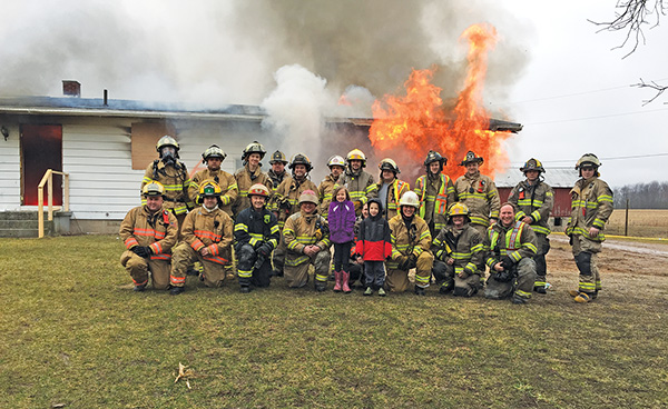 Pictured here with area firefighters is Taylor and Eli Gunderson, during the last burn on their old home. Courtesy photo.