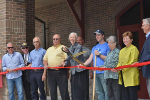 The ceremonial ribbon cutting at the new Cedar Springs Community Library. From L to R: Duane McIntyre, licensed builder; Solon Township Supervisor Bob Ellick; Cedar Springs Mayor Gerald Hall; Library Director Donna Clark; CS City Manager Michael Womack; Lakeland Library Coop Director Sandra Wilson; Claudia and Tom Mabie, representatives of the Community Building Development Team. Not shown are Mayor Pro Tem Pam Conley (to the far left of Duane McIntyre) and Kurt Mabie, Chair of the CBDT (to the right of Tom Mabie). Photo by Kathy Anderson.